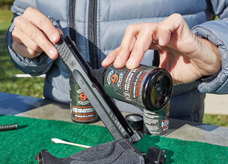 Shooter cleaning pistol with Hoppe's Black High-Performance Precision Oil