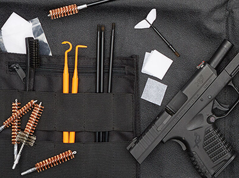 Handgun laid out on a Hoppe's Range Kit with Cleaning Mat